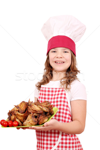 Happy little girl cook with roasted chicken wings Stock photo © goce