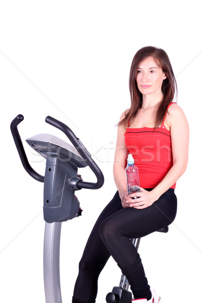 girl with bottle of water sitting on cross trainer Stock photo © goce