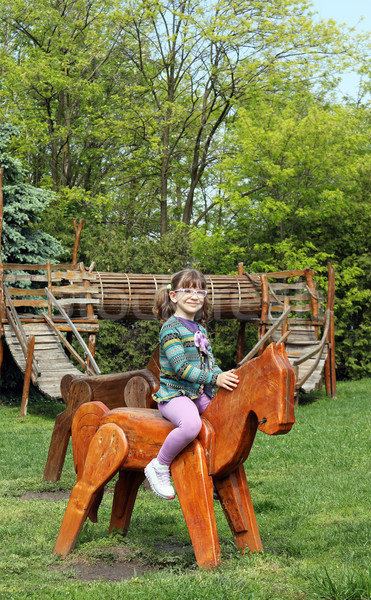 happy little girl riding wooden horse Stock photo © goce