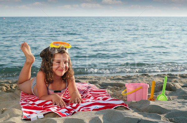happy little girl with diving mask lying on beach Stock photo © goce