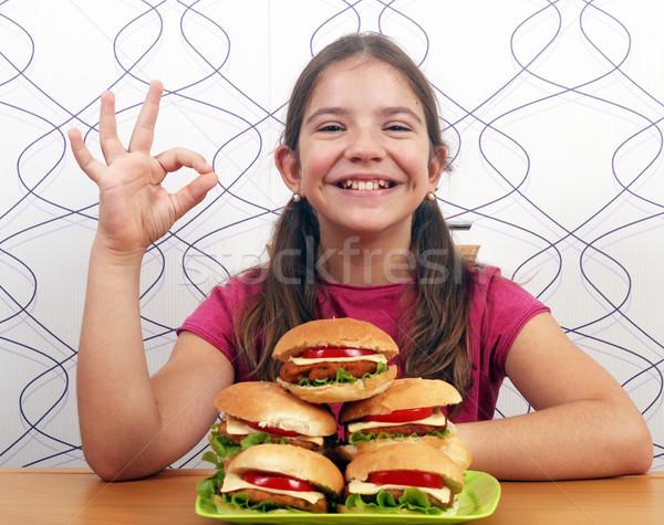 Boldog kislány hamburgerek kézjel étel mosoly Stock fotó © goce