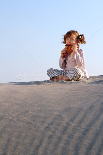 happy little girl play pan pipe in desert Stock photo © goce