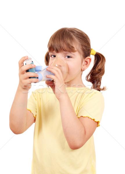 Stock photo: little girl using an asthma inhaler