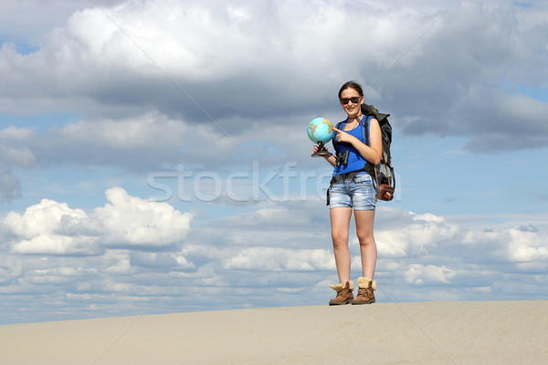 girl hiker looking at a globe where they will travel Stock photo © goce