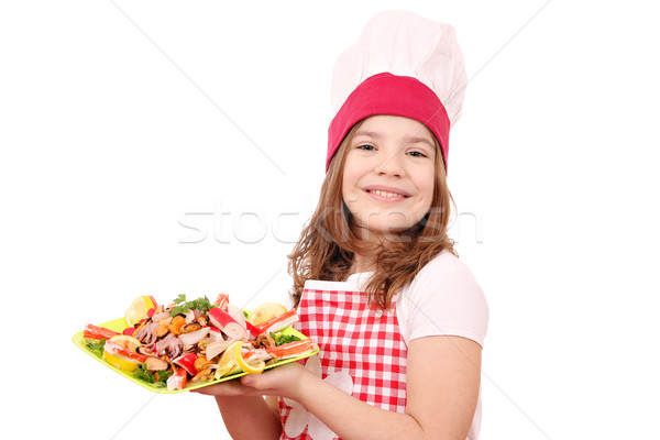 Stock photo: happy little girl cook with seafood on plate