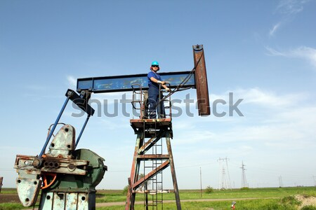 Stock photo: oil worker on pump jack
