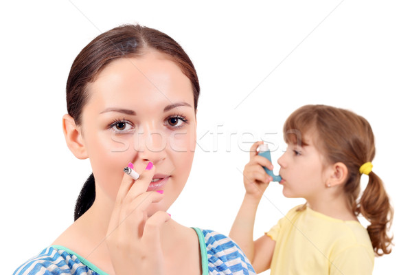 girl smoking cigarette and little girl with inhaler Stock photo © goce