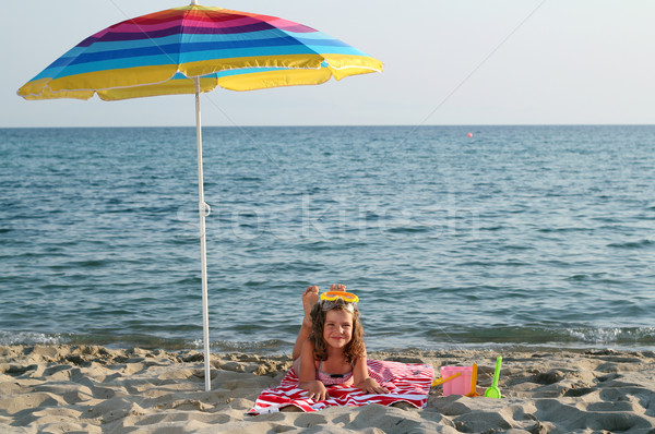 little girl with diving mask lying under sunshade on beach Stock photo © goce