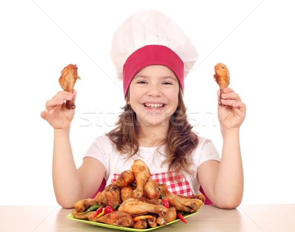 happy little girl cook holding chicken drumsticks Stock photo © goce