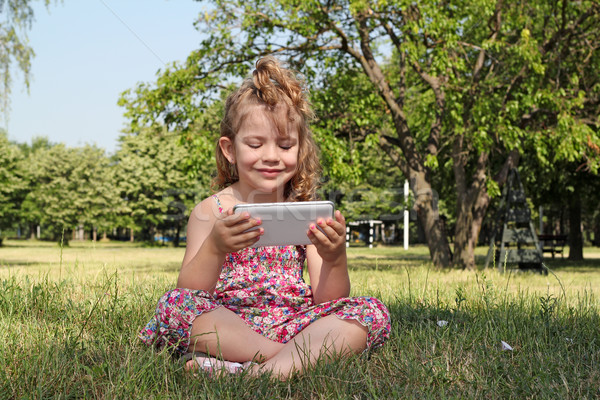 little girl sitting in park and play with tablet pc Stock photo © goce