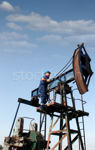 oil worker climbs up to the pump jack Stock photo © goce