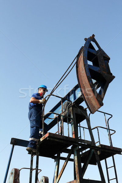 oil worker climb on pump jack Stock photo © goce