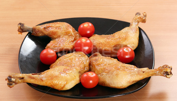 chicken drumstick and tomatoes on black dish Stock photo © goce