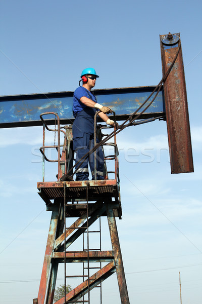 oil worker in blue uniform standing at pump jack Stock photo © goce