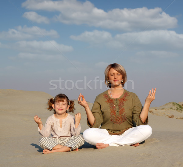 Stock photo: mother and daughter meditating in desert