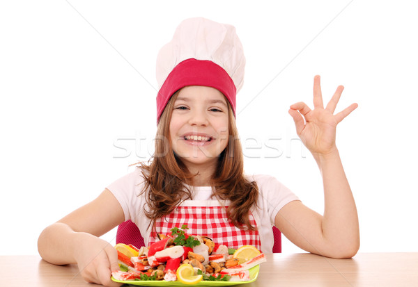 Stock photo: happy little girl cook with seafood and ok hand sign