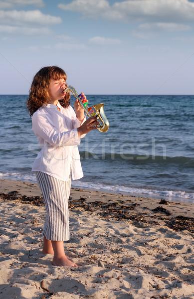 beautiful little girl play saxophone on beach Stock photo © goce