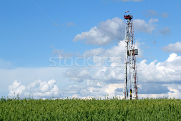 oil drilling rig on green wheat field Stock photo © goce