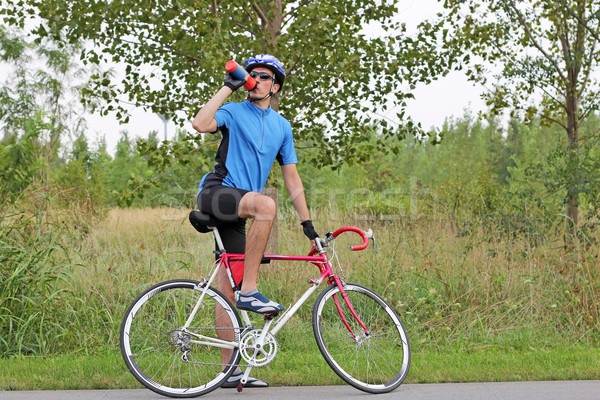 male cyclist sitting on race bike and drink water Stock photo © goce