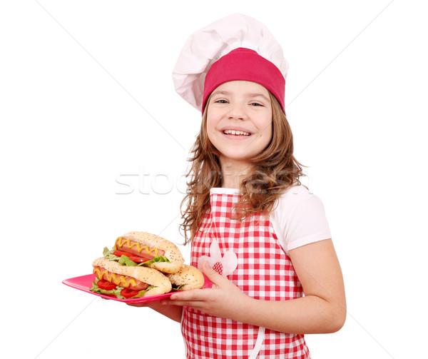 Mutlu küçük kız pişirmek sıcak köpekler plaka Stok fotoğraf © goce