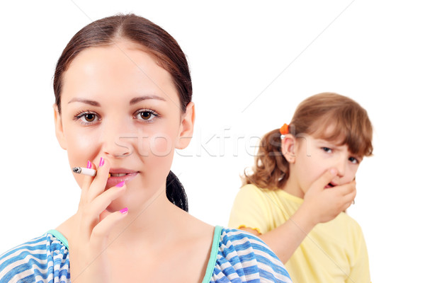 girl smoking cigarette and little girl coughs Stock photo © goce