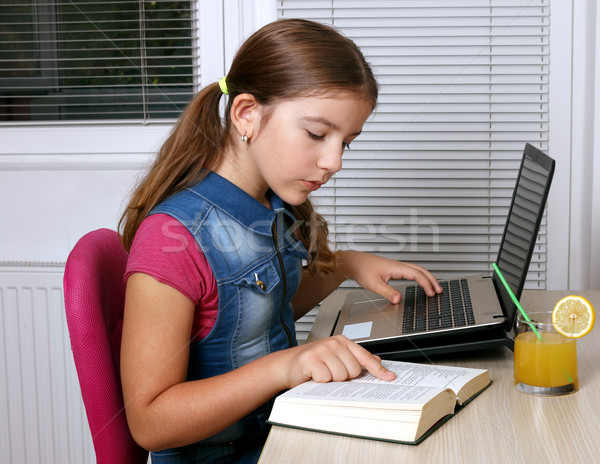 little girl studies with a book and a laptop at home Stock photo © goce