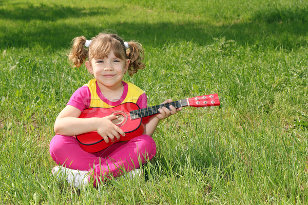 happy little girl with guitar sitting on grass  Stock photo © goce