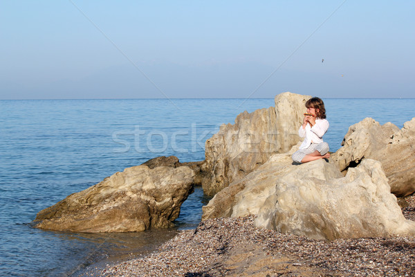 little girl sitting on a rock by the sea and playing pan pipe Stock photo © goce