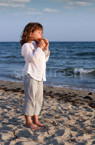 beautiful little girl play pan pipe on beach Stock photo © goce