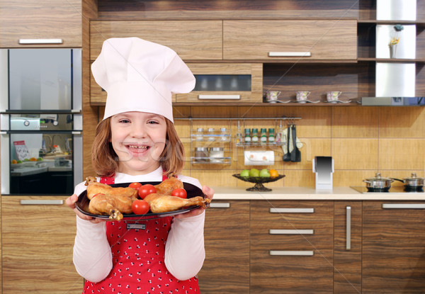happy little girl cook hold dish with chicken drumstick in kitch Stock photo © goce