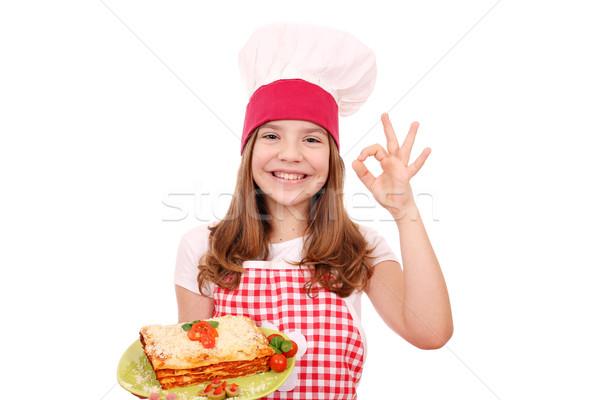 Feliz little girl cozinhar lasanha sinal da mão Foto stock © goce