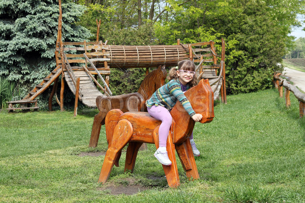 little girl riding wooden horse on playground Stock photo © goce