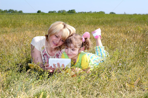 mother and daughter are having fun with tablet Stock photo © goce