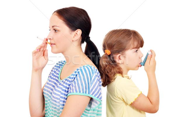 girl smoking cigarette and little girl use inhaler Stock photo © goce