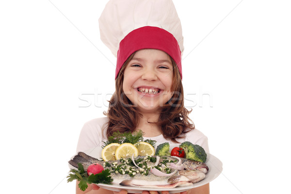 happy little girl cook with prepared trout fish on plate Stock photo © goce