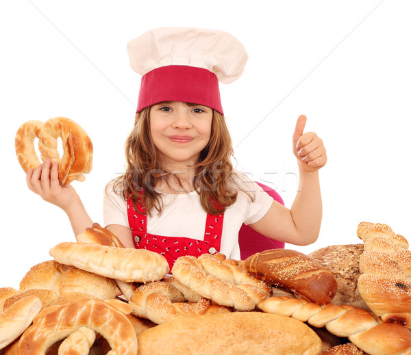 Feliz little girl cozinhar pretzel polegar para cima Foto stock © goce