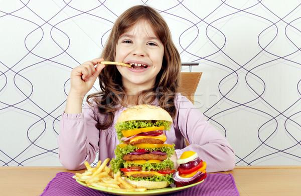 Głodny dziewczynka jeść duży hamburger frytki Zdjęcia stock © goce