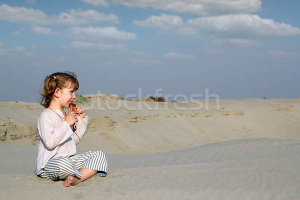 little girl sitting on sand and play music Stock photo © goce