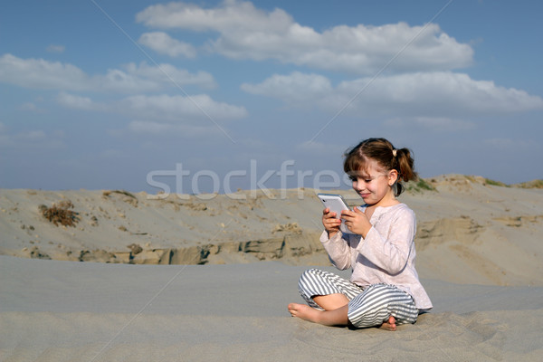 Stock photo: little girl play with tablet pc in desert