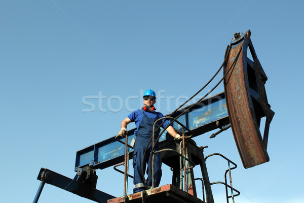 oil worker standing on pump jack Stock photo © goce