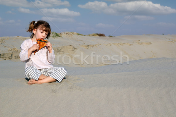 little girl play panpipe in desert Stock photo © goce