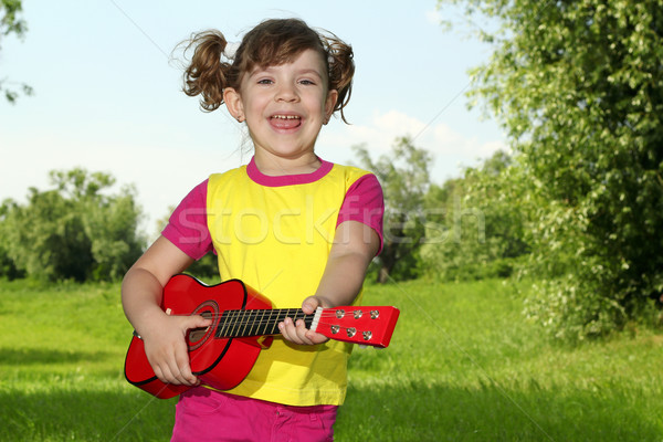 happy little girl play guitar and sing Stock photo © goce