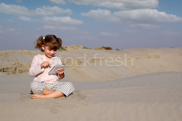happy little girl play with tablet pc in desert Stock photo © goce