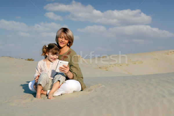 mother and daughter play with tablet in desert Stock photo © goce