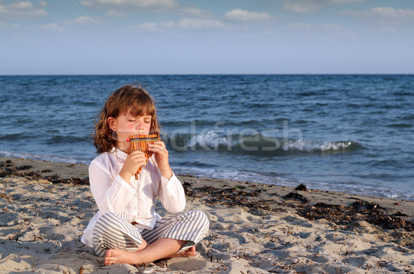 beautiful little girl sitting on beach and play pan pipe Stock photo © goce