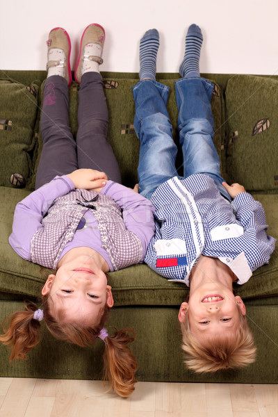 little girl and boy lying upside down on the bed Stock photo © goce