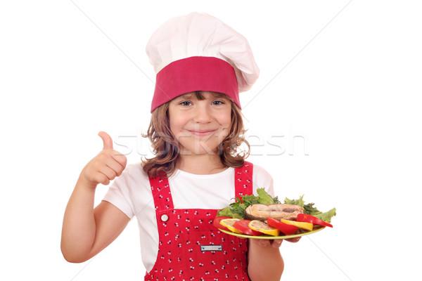 Bambina cuoco salmone frutti di mare pollice up Foto d'archivio © goce