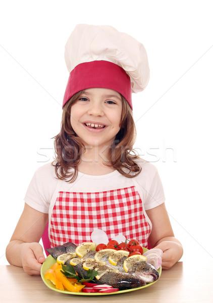 Felice bambina cuoco preparato pesce piatto Foto d'archivio © goce