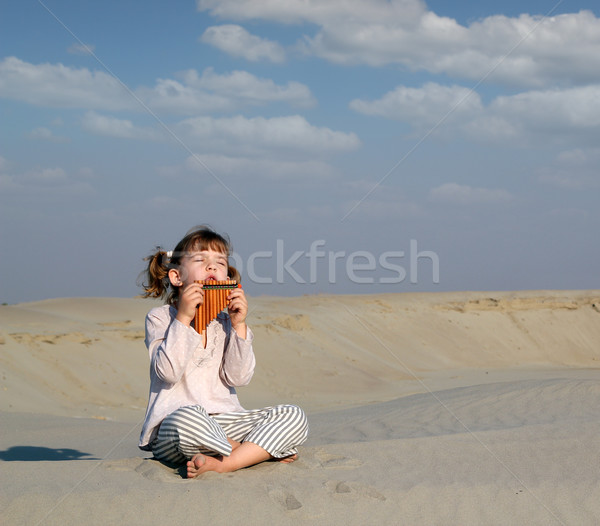 little girl play music on pan pipe in desert Stock photo © goce