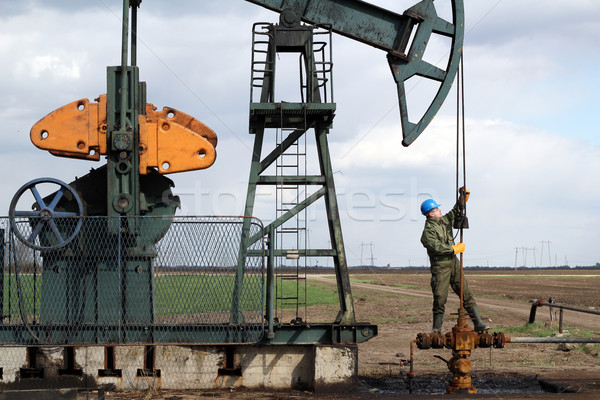 oil worker standing at pipeline and check pump jack Stock photo © goce